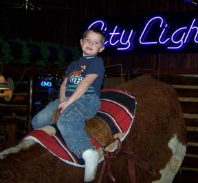 Photo: Young kid riding mechanical bull